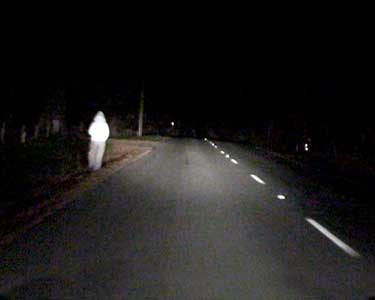 Here is the stranger walking along a dark country road ...